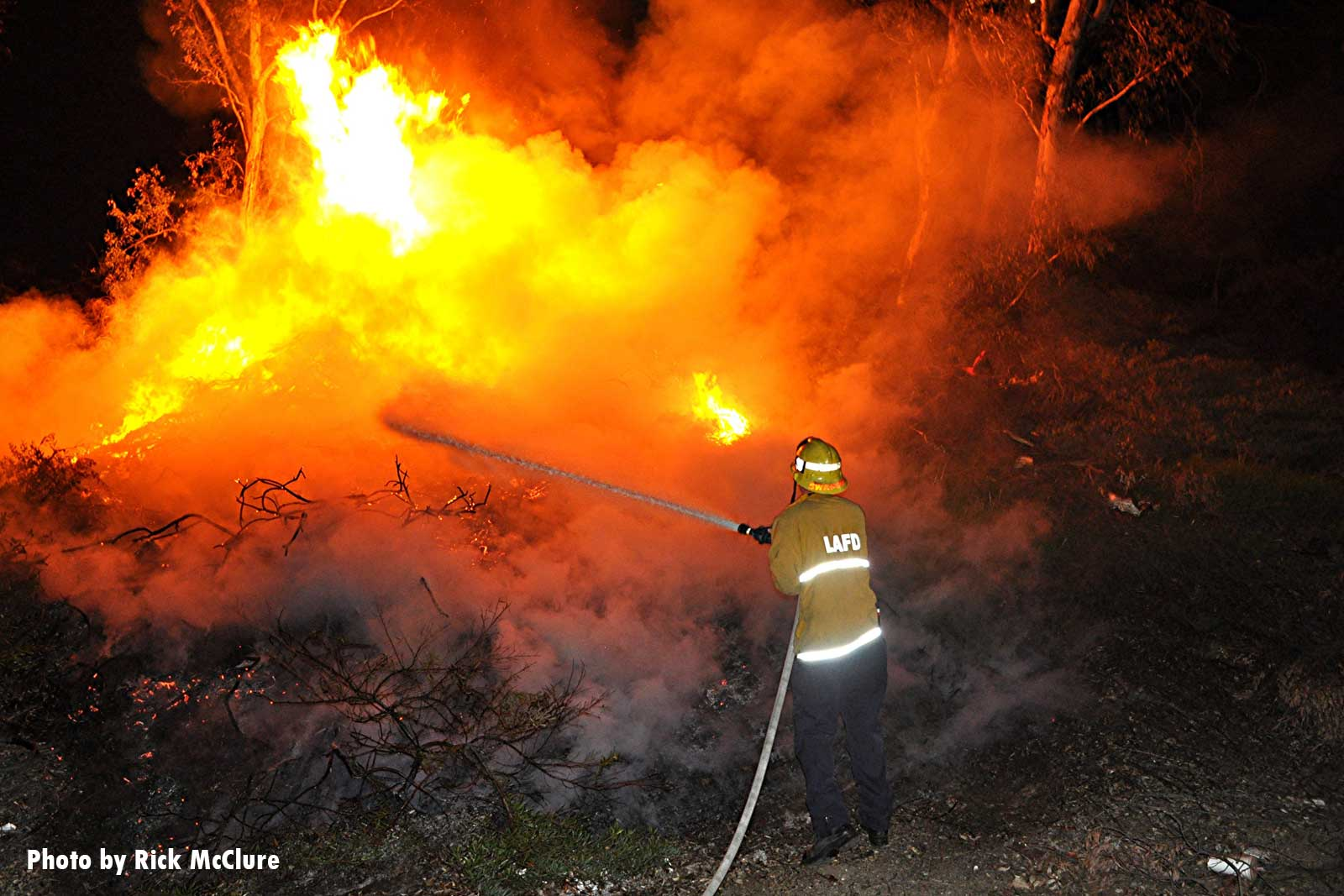 A firefighter aims a hose stream at burning brush in California