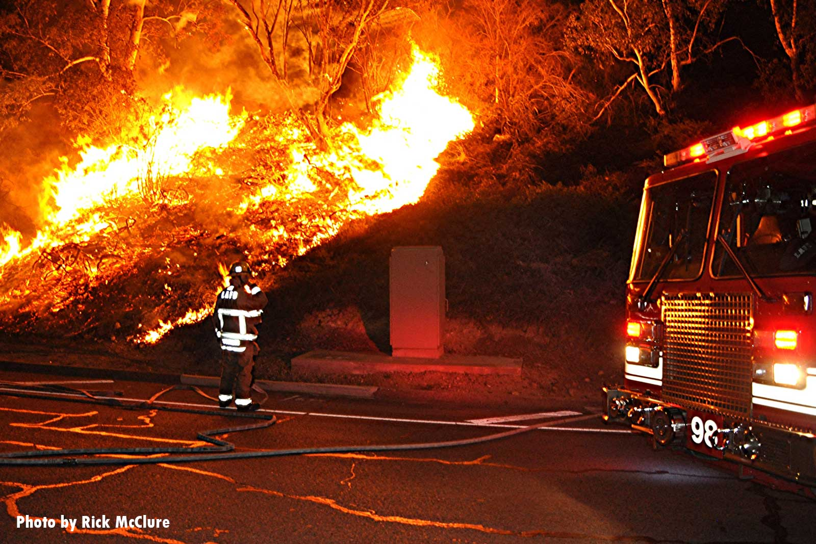 LAFD firefighters at the scene of a fire blazing in vegetation