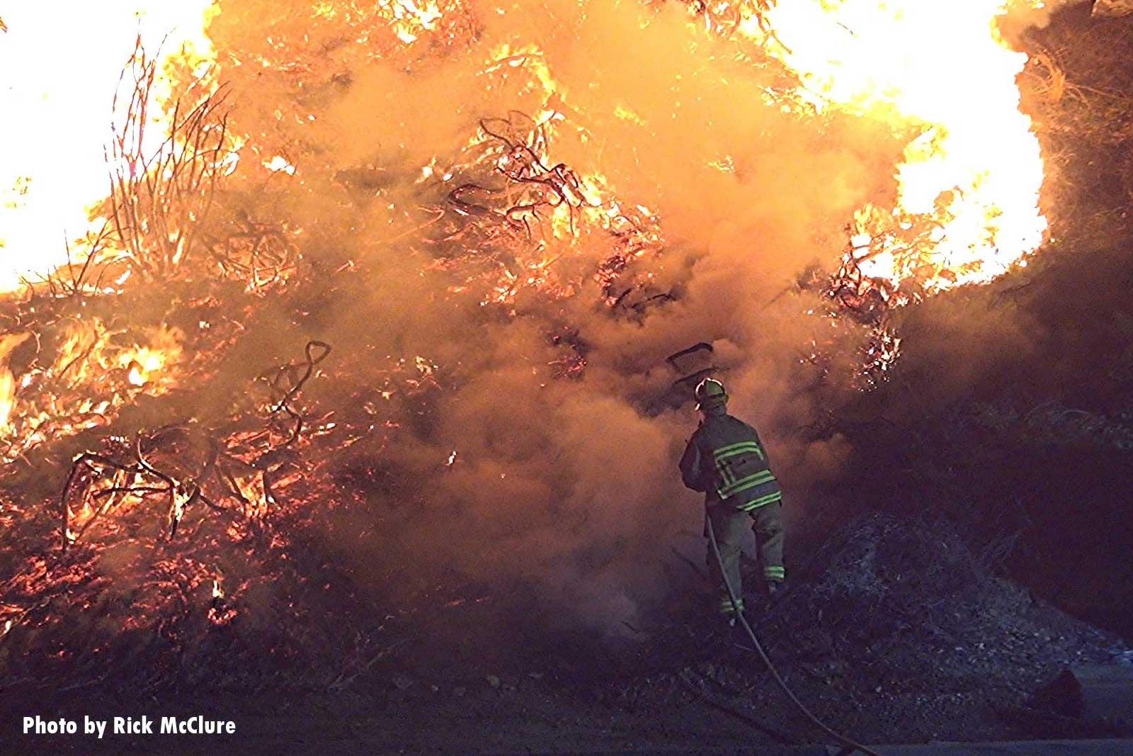 A firefighter advances a hose up a burning hill