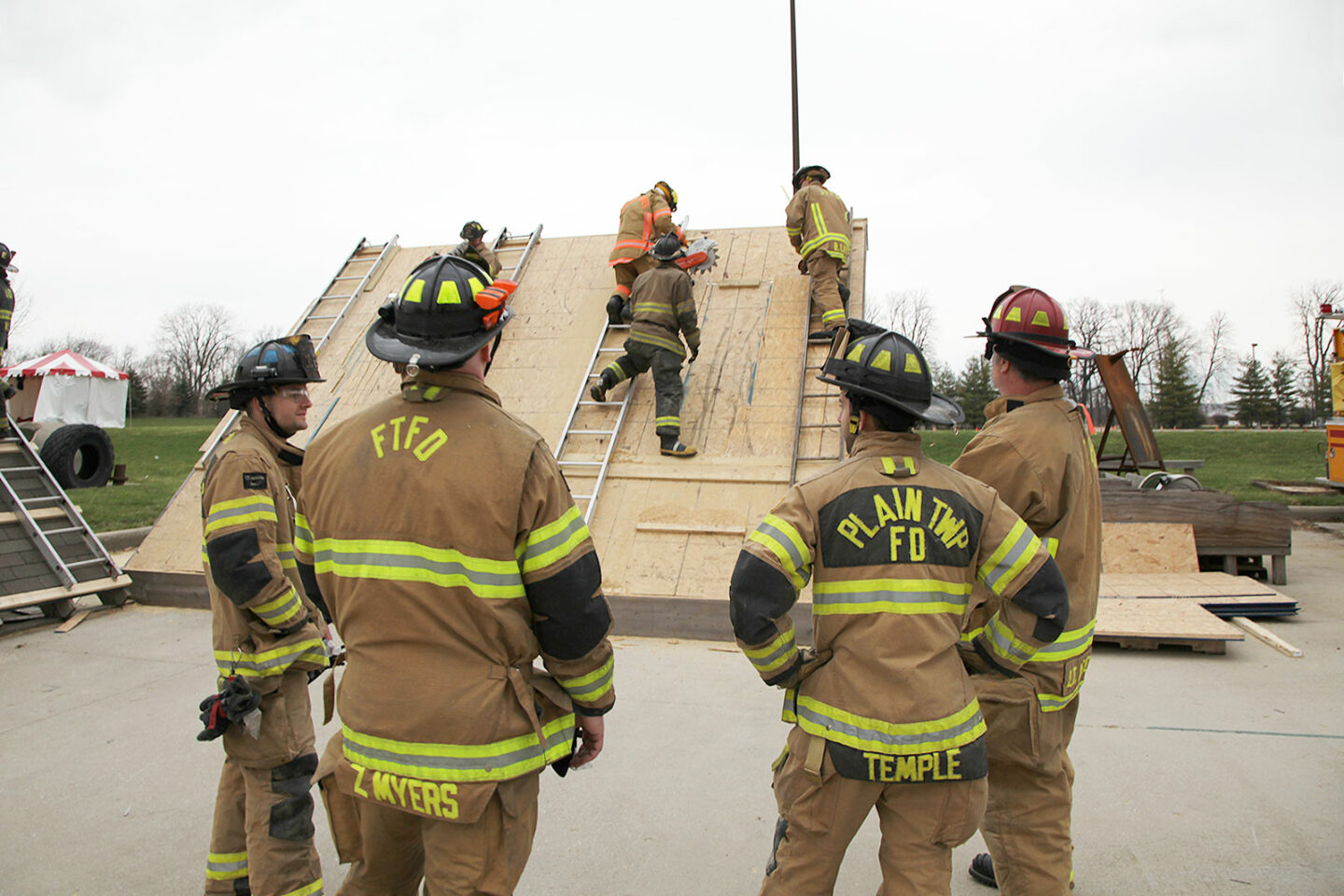 Firefighters with power saws training vertical ventilation on roof props