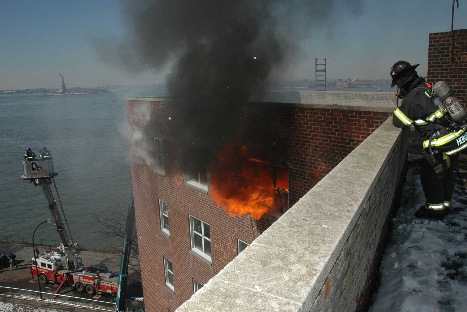 FDNY firefighter at abandoned apartment building in NYC watching fire and smoke blow out a window