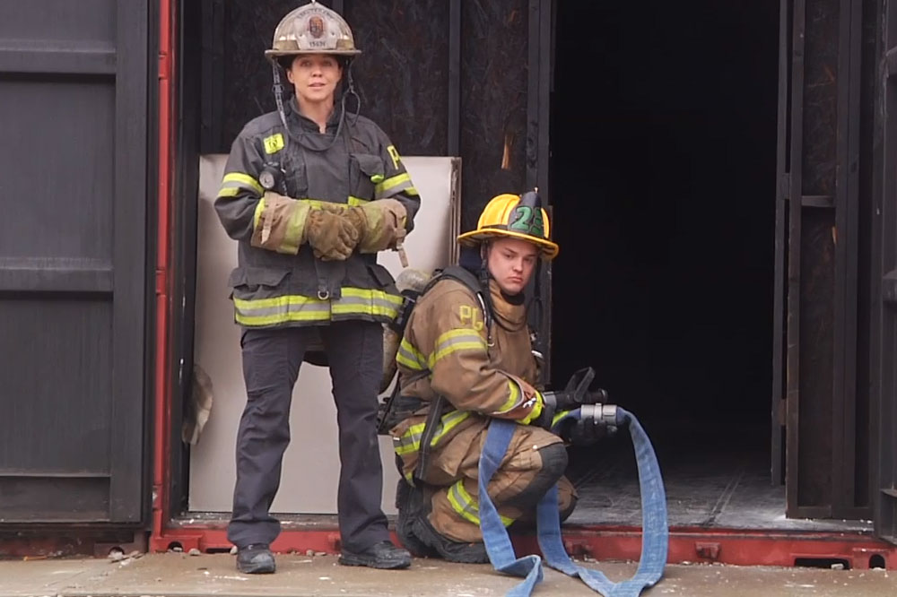 Katie Johnson and another firefighter with a hoseline