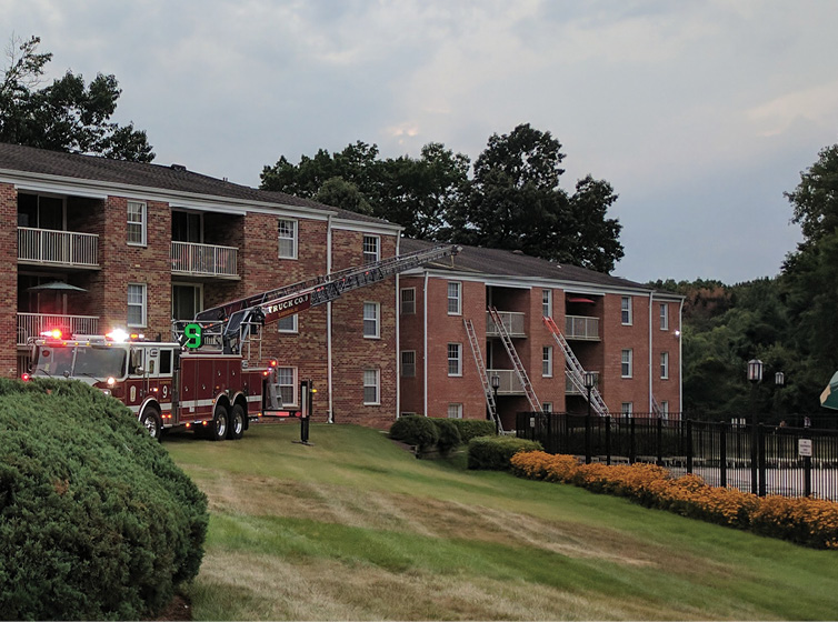 Positioned on side C of an apartment fire, this truck backed in and was able to reach the apartment building's roof. As a result, the ladder bed was closer to the building and it was easier to get ladders in place. Even with uneven topography, they could navigate through the grass and gain access to the building.