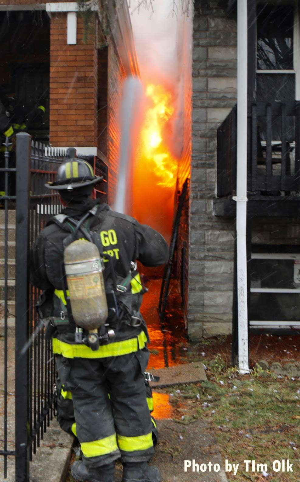 A firefighter uses a hose stream to limit fire spread to an exposure building
