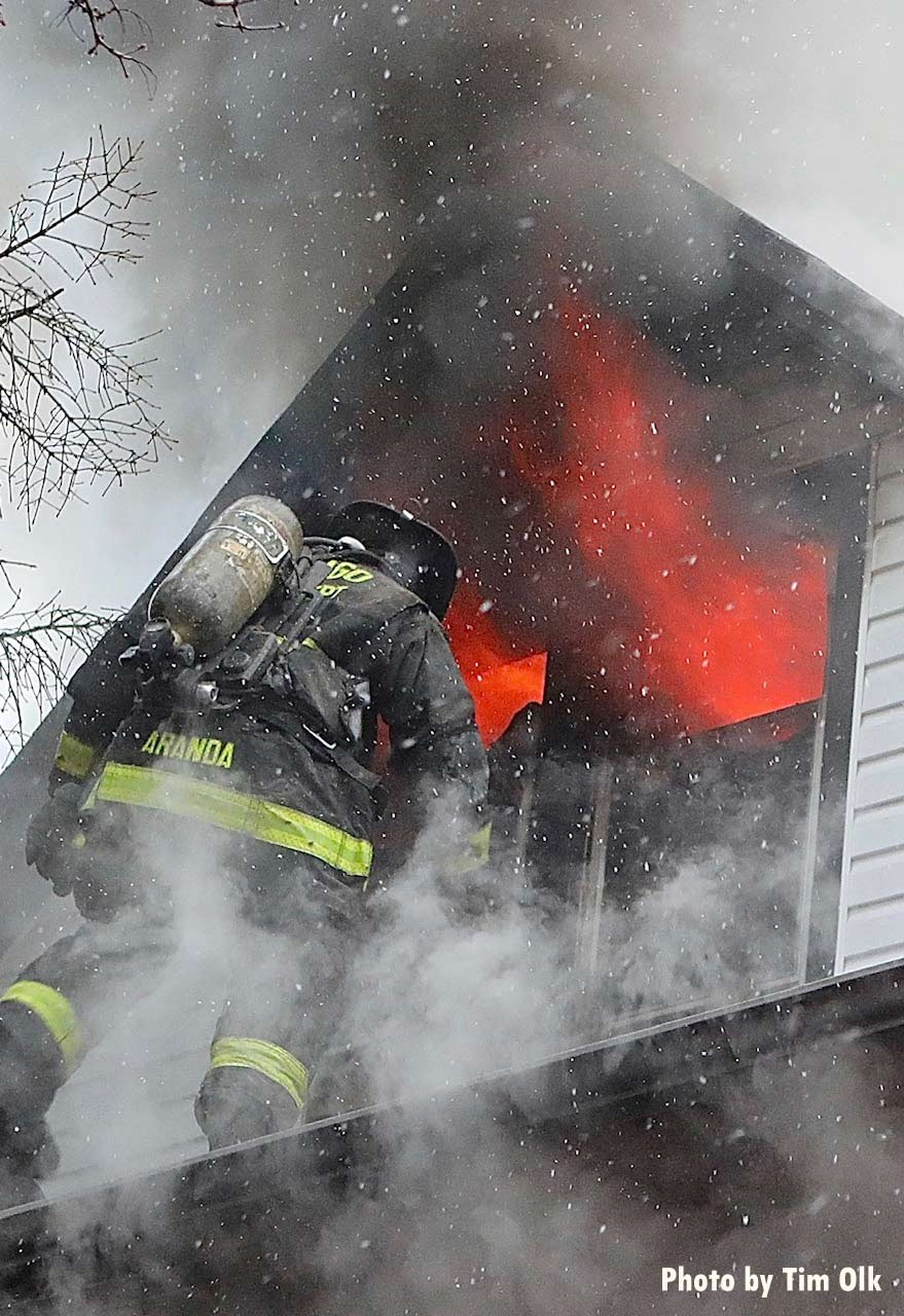 Flames shoot out from an upper story as a firefighter operates on the roof