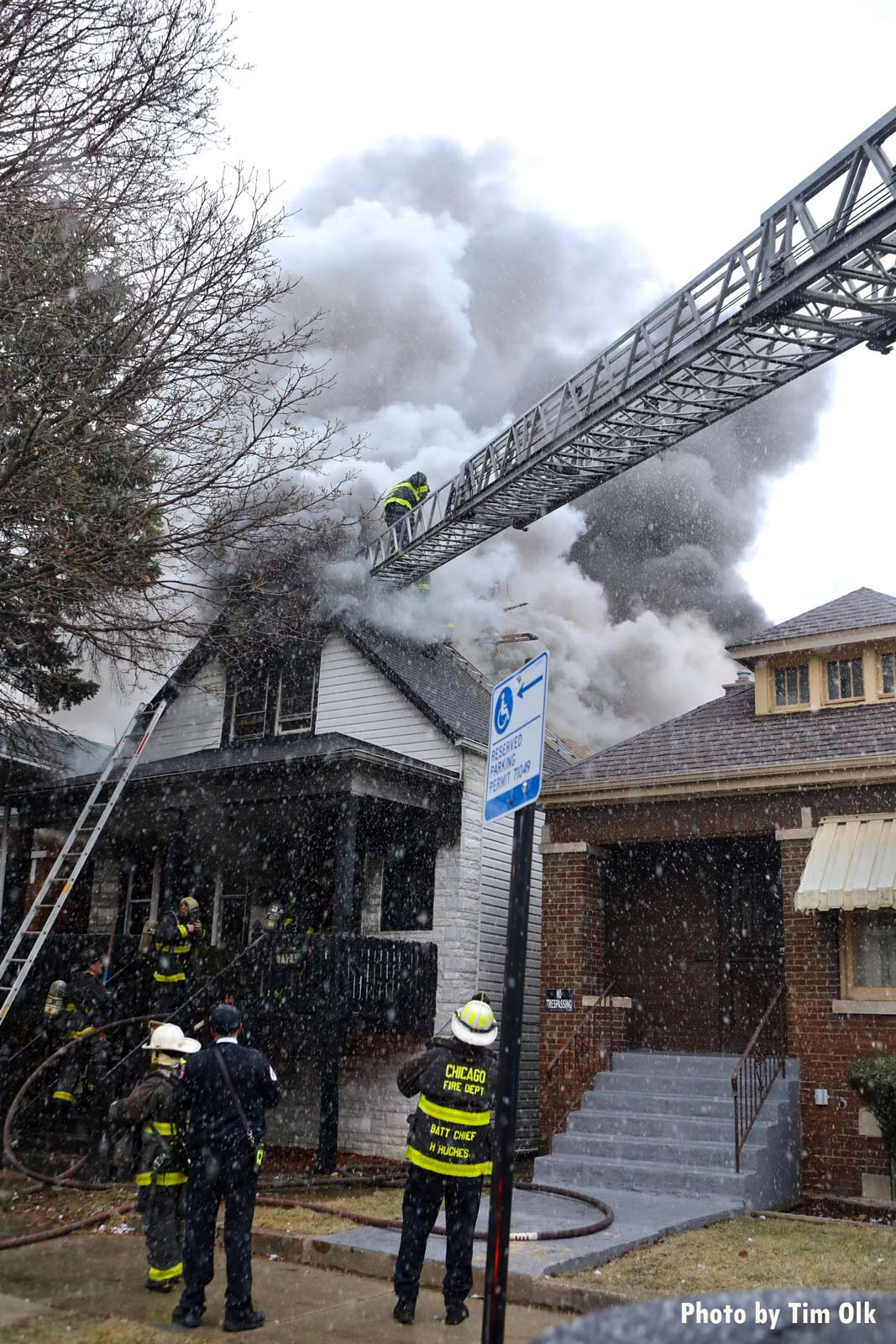 Aerial ladder directed to roof of burning building