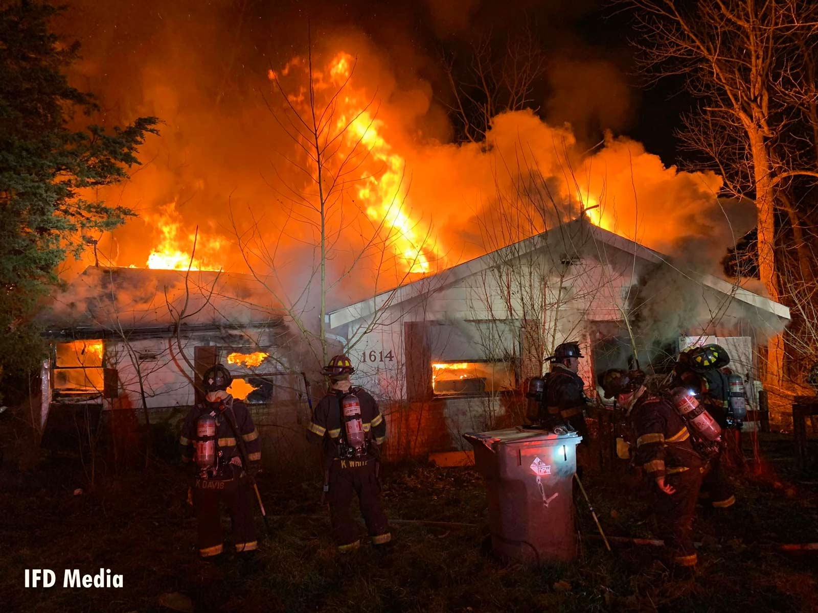 Firefighters work on the exterior of a burning home