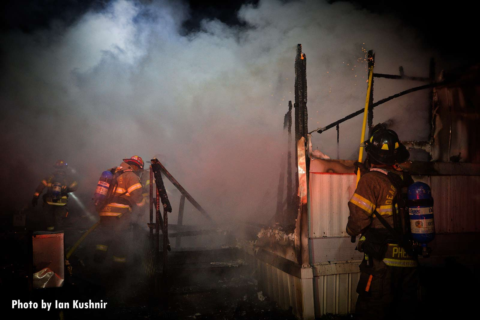 Firefighters work among the ruins of burned mobile home in Dearborn Heights