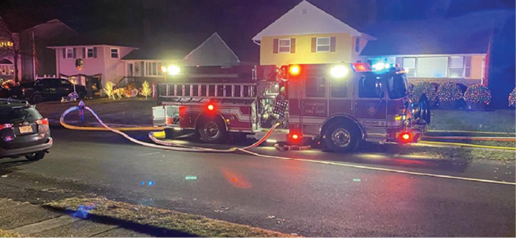 """Engine 2 is positioned two houses away with a positive water supply of one five-inch and one three-inch supply line. Its driver's side wheels are up on the sidewalk and the apparatus is partially """"beached"""" to allow additional apparatus access to the front of the fire building."""