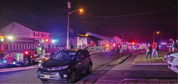 An overview of the fireground operation, including the placement of the ladder truck with the body directly under the communication wires. Positioning the ladder truck in this manner sometimes takes the hazard of the overhead wires out of the equation. Truck operators must always exercise caution around overhead obstructions.
