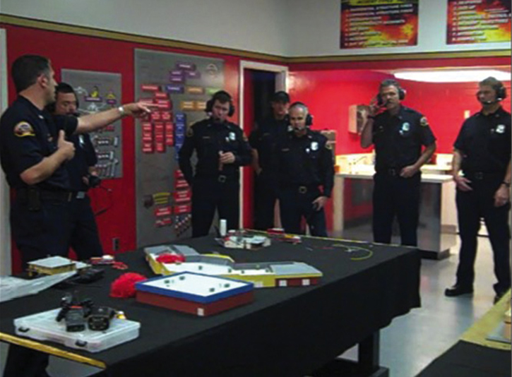 Company officers training on a tabletop model with radios.