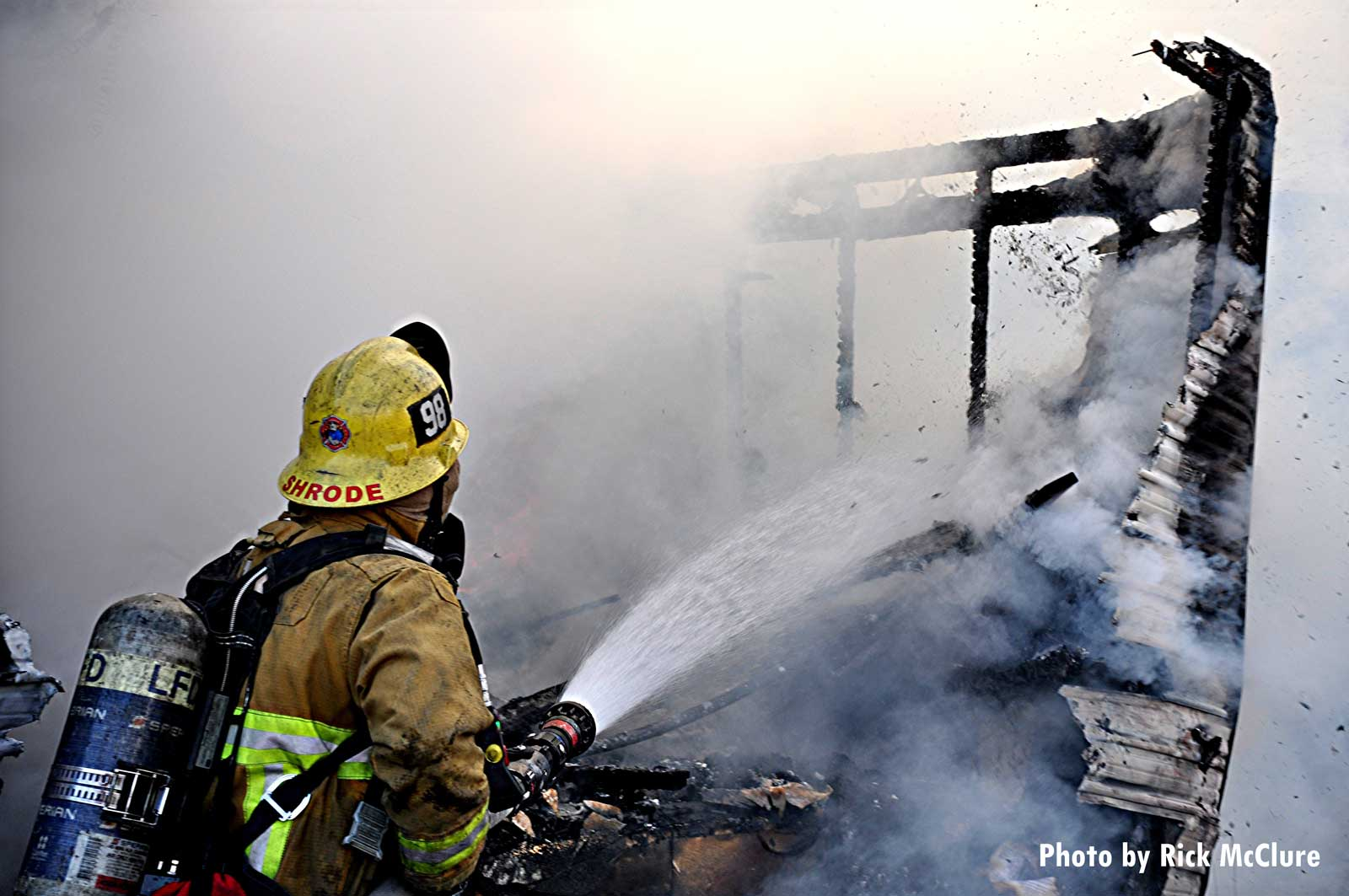 Firefighter turns a hoseline on a trailer fire