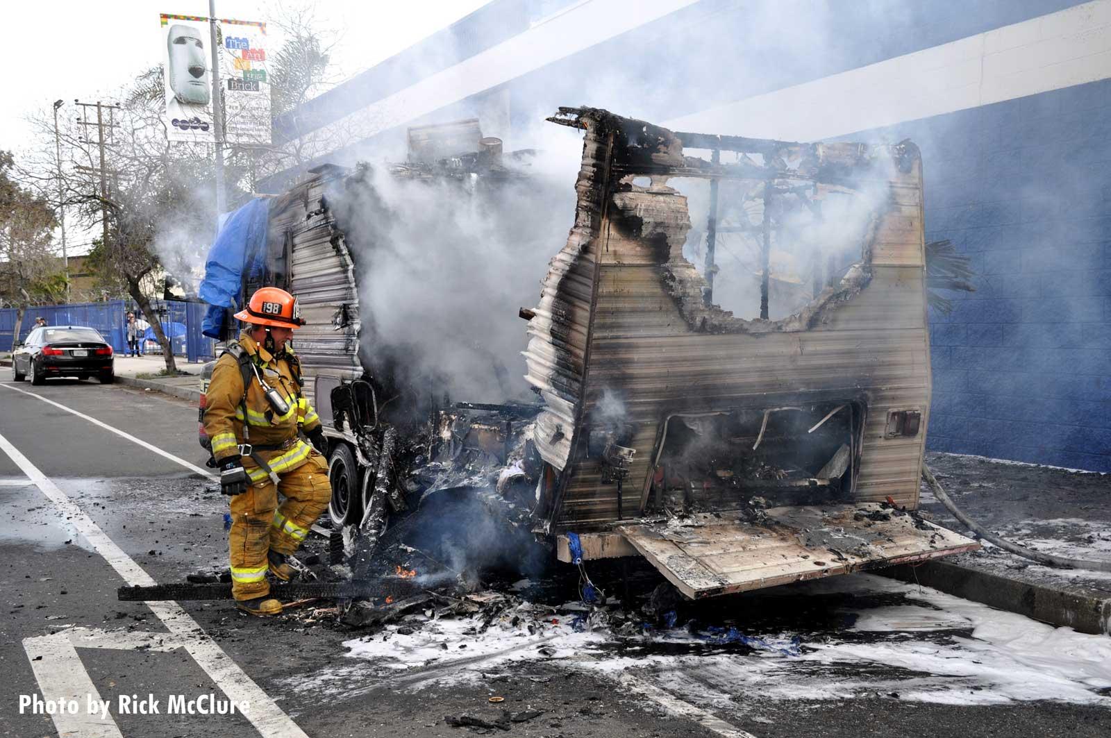 Firefighter navigating around wreckage of burnt trailer