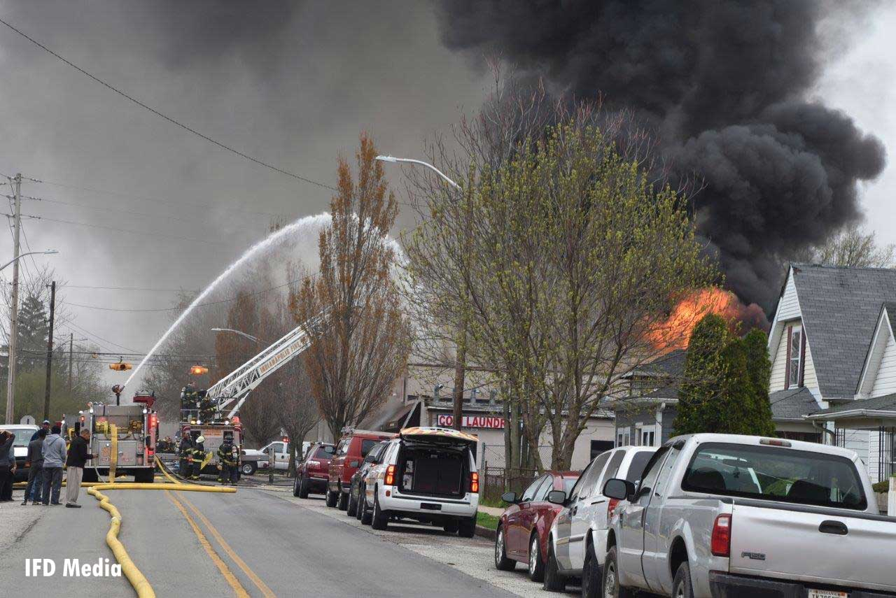 Multiple streams are trained on fire as flames vent from the building