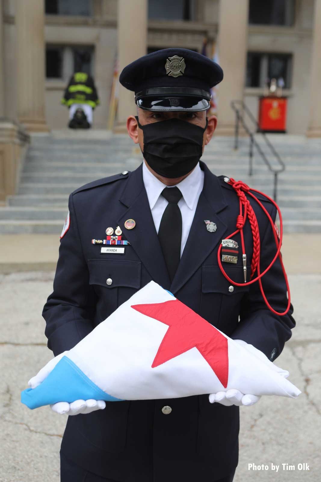 In a mask due to the coronavirus, a Chicago firefighter at the funeral
