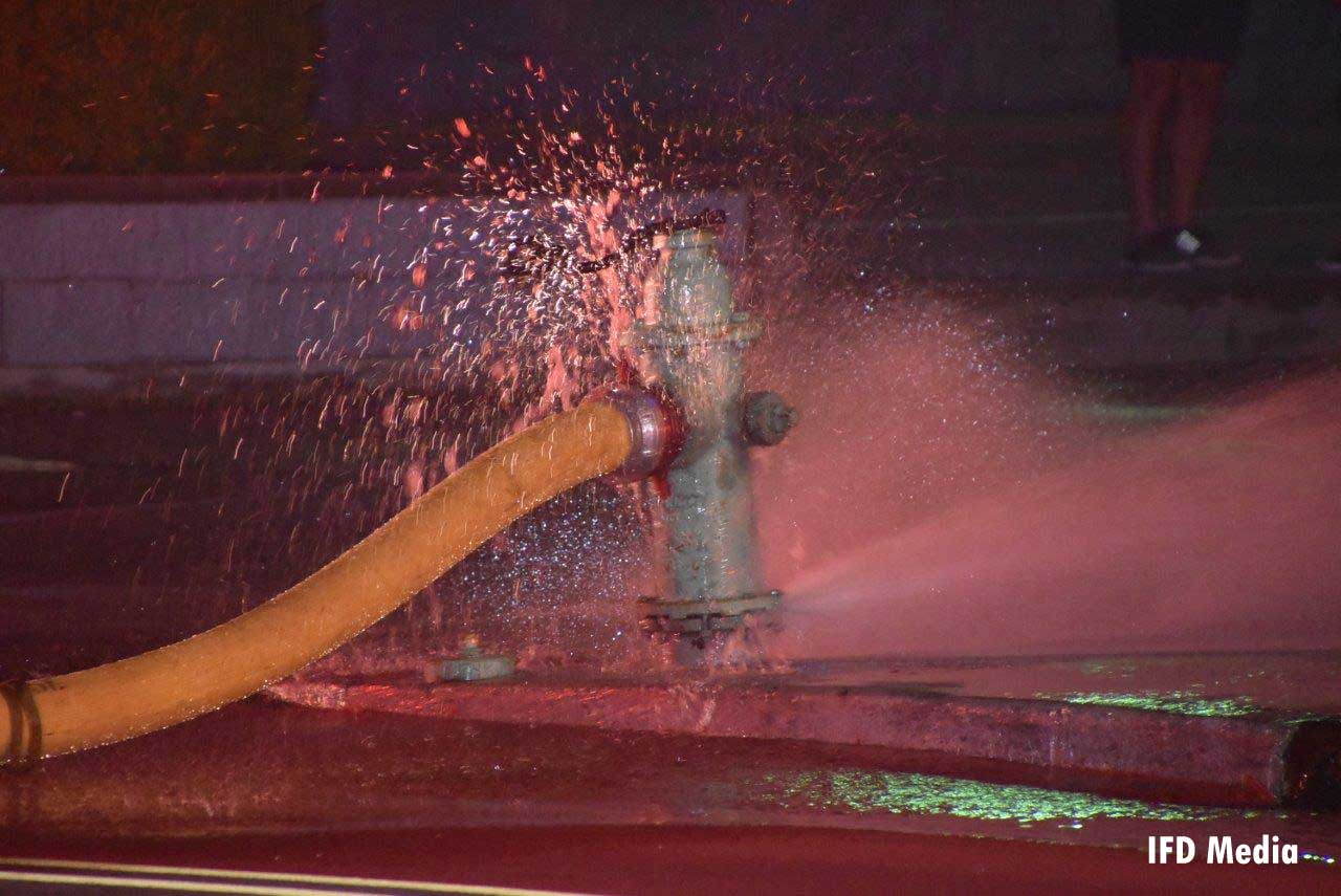 Fire hydrant with supply line spraying water