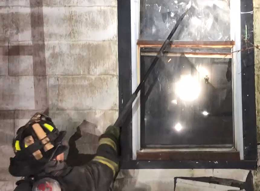 Firefighter taking the window with a hook