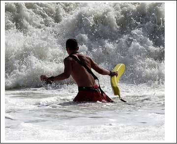 Lifeguard entering the surf with a rescue tube