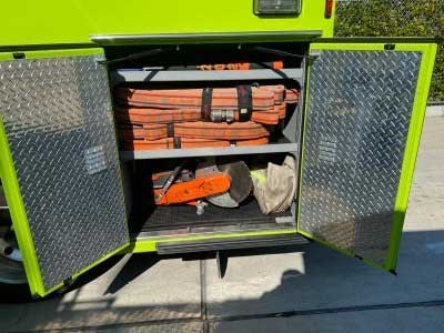 Hose bundles and saws stowed in a fire apparatus compartment