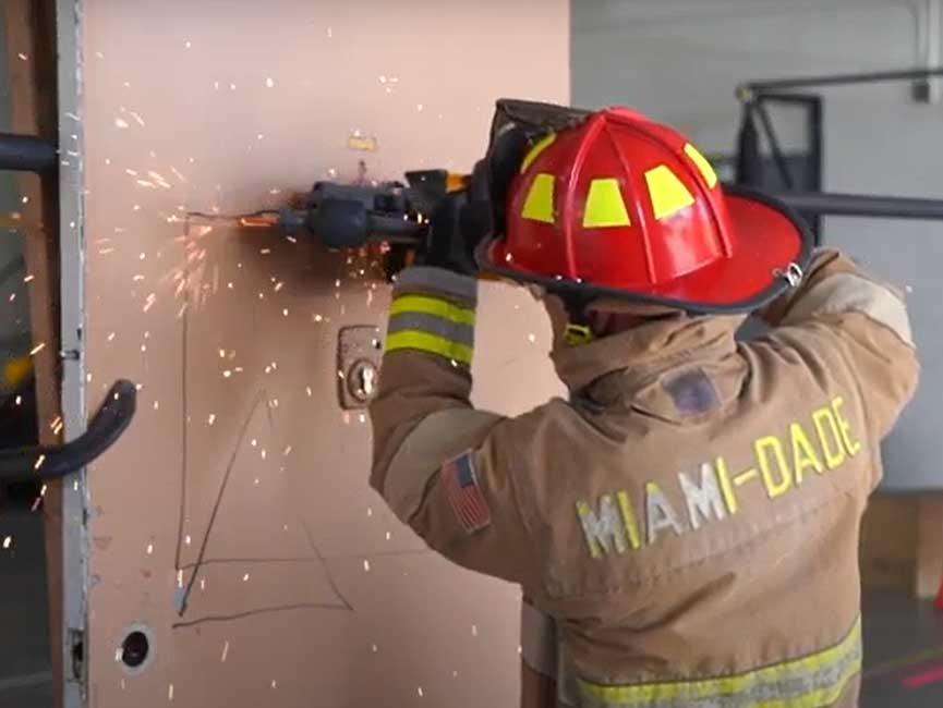 A Miami-Dade firefighter cuts a door with a Mul-T-lock