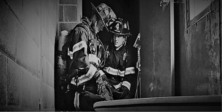 Two modern firefighters contemplate the delicate balance between tradition and innovation.