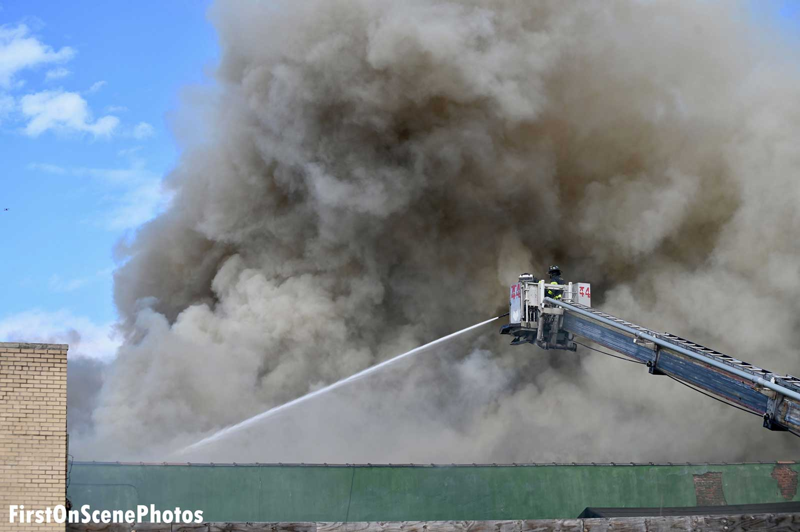 A firefighter in a tower ladder bucket trains a water stream on the fire building