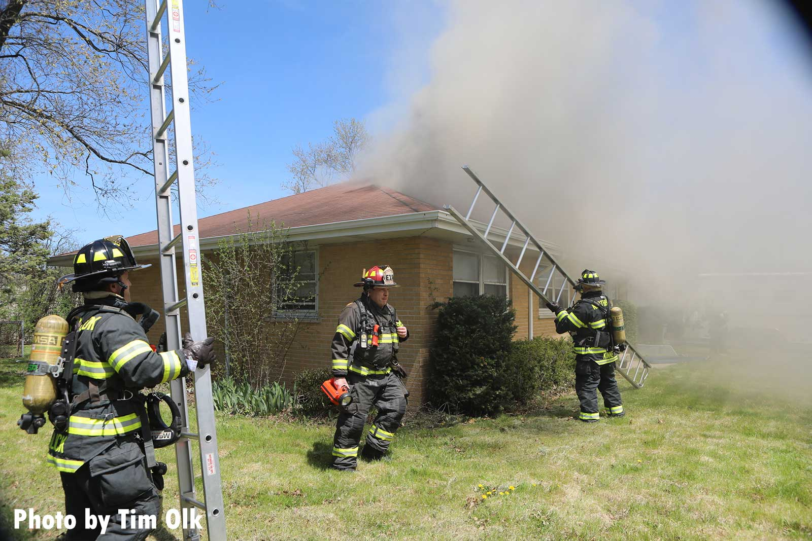 Firefighters begin to raise ladders at the home