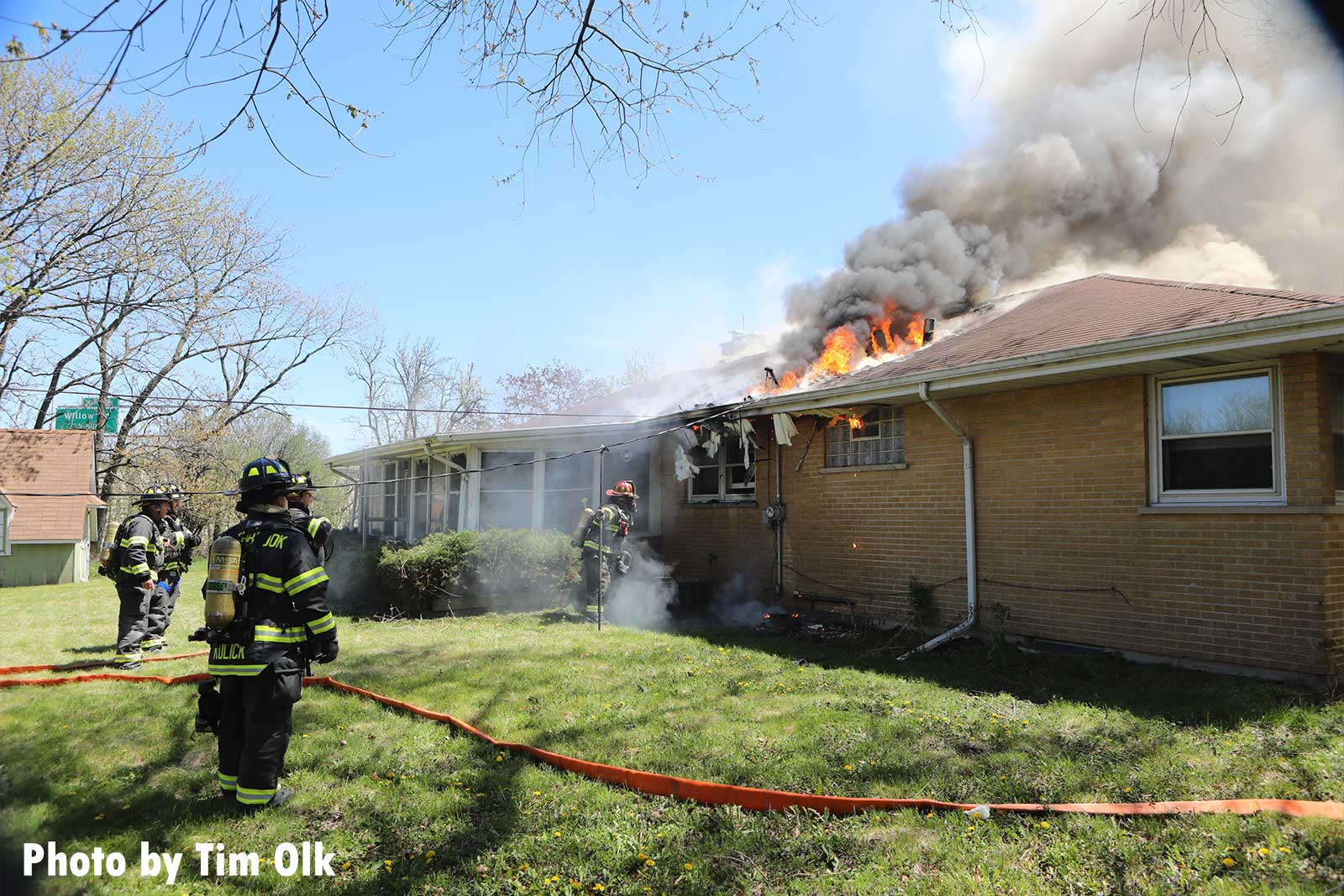 Firefighters move hose at the Northbrook house fire