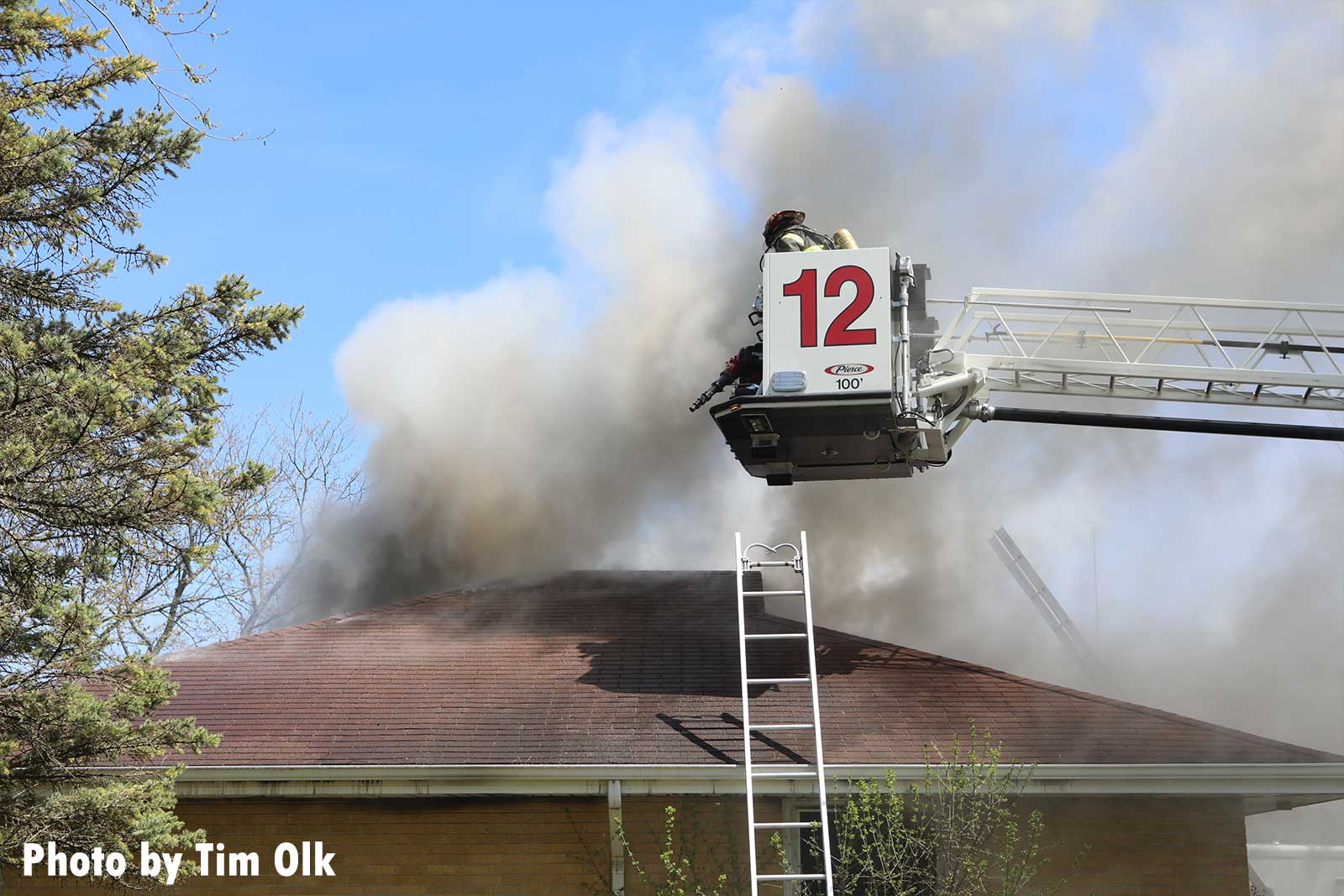 Firefighters in tower ladder bucket over house fire