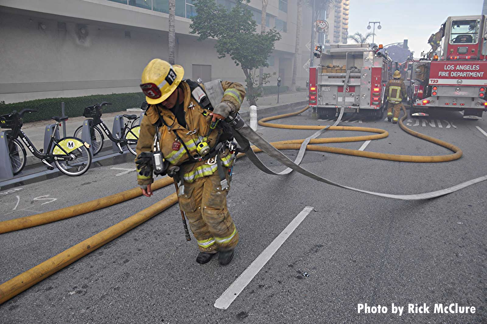 Firefighter hauls hoselines at explosion in downtown Los Angeles