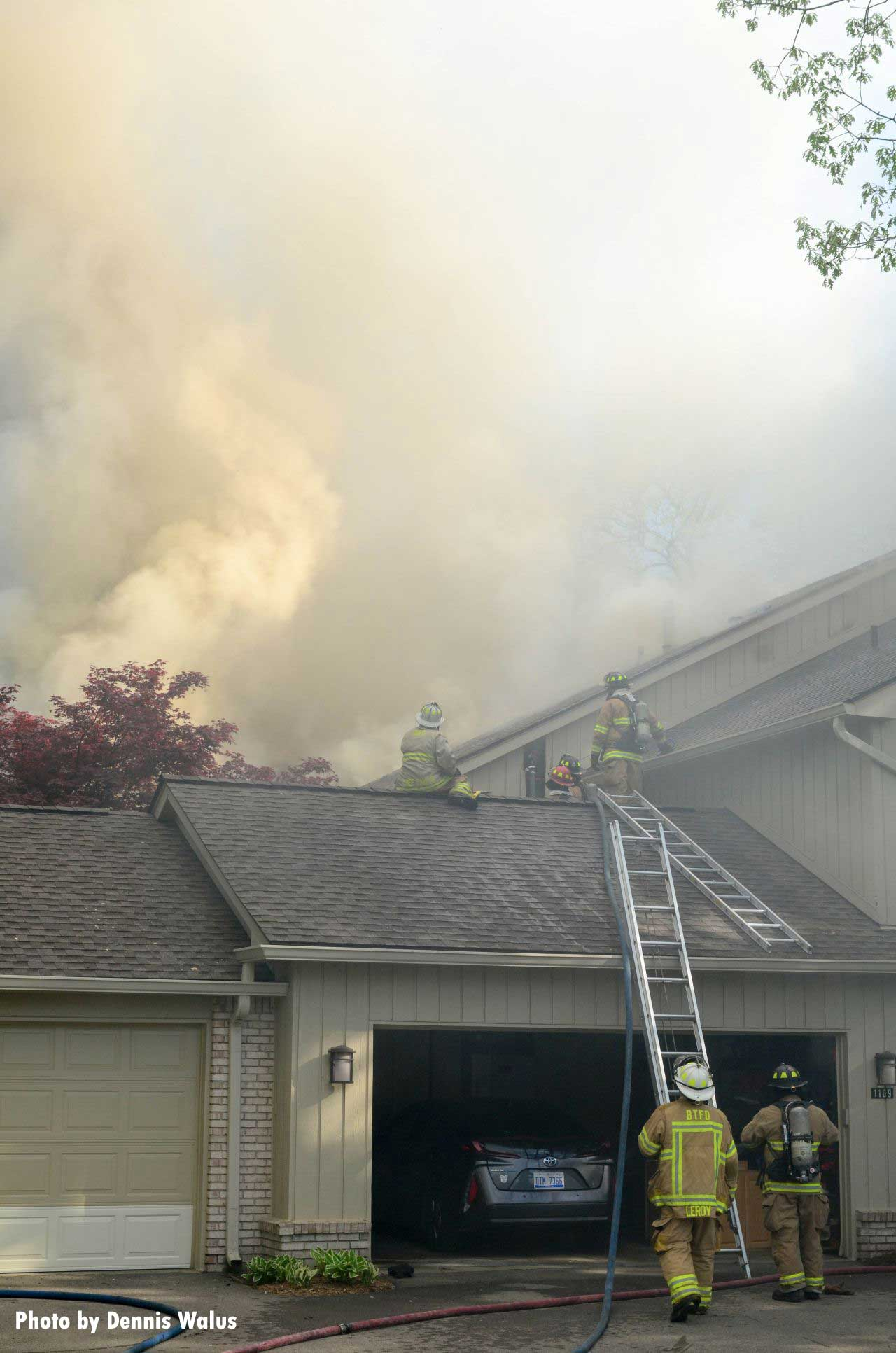 Firefighters on the roof with smoke billowing out of the condo