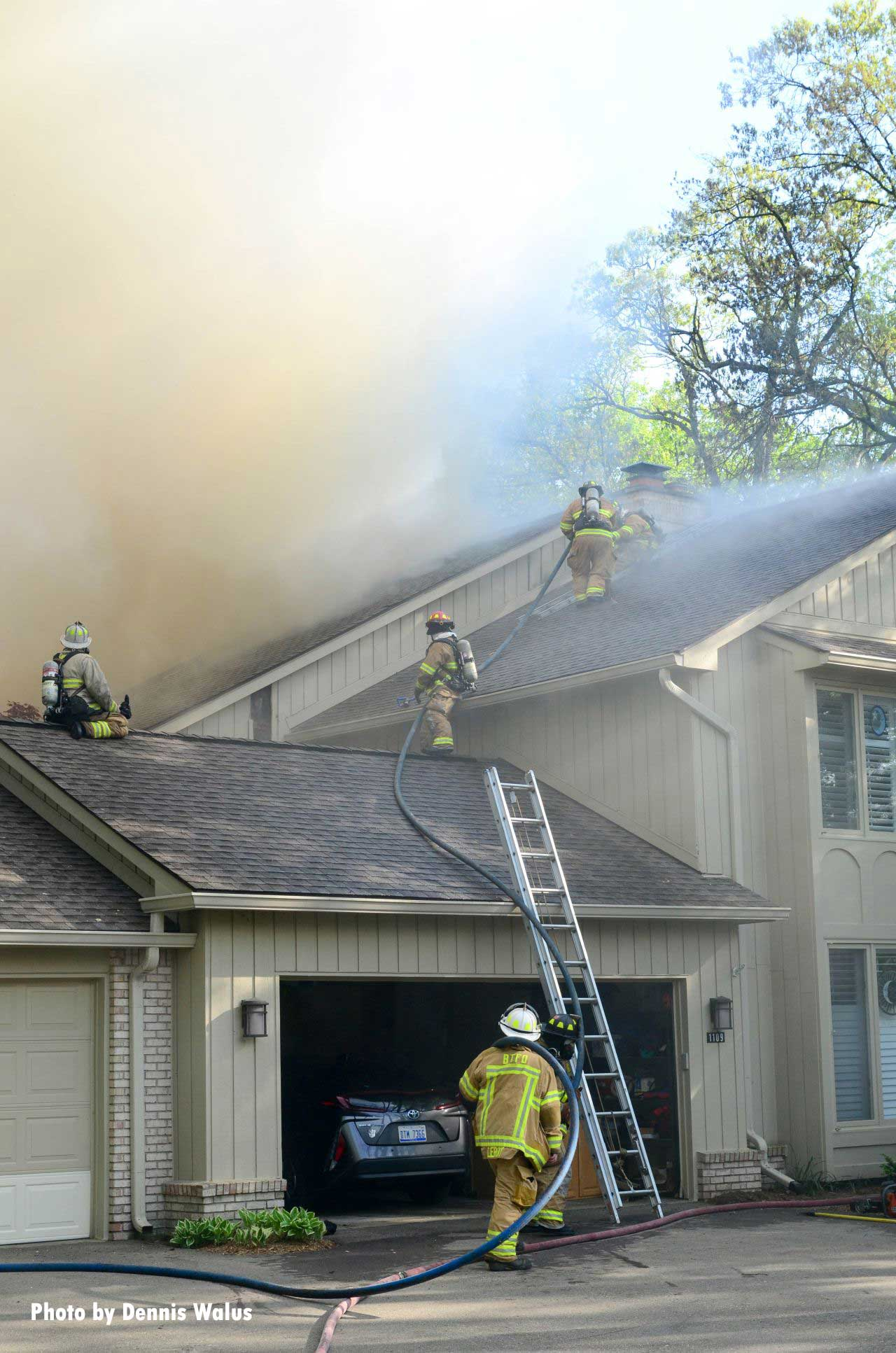 Firefighters operate on the roof of the building during a condo fire
