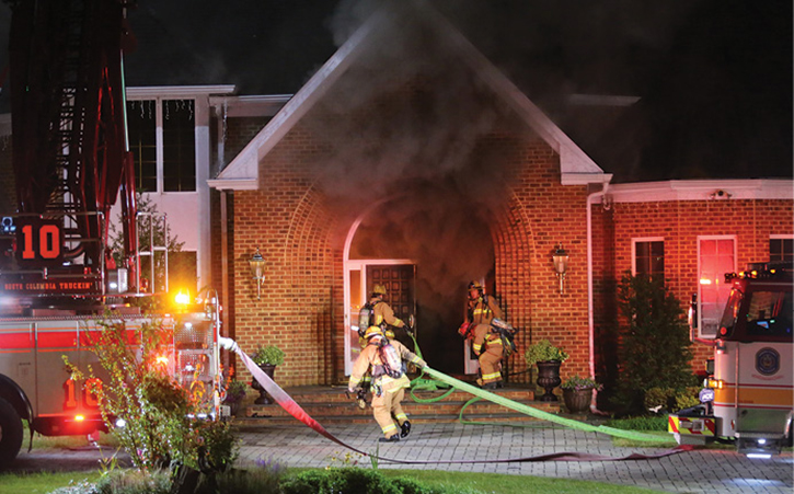 Firefighters pulling lines at fire scene
