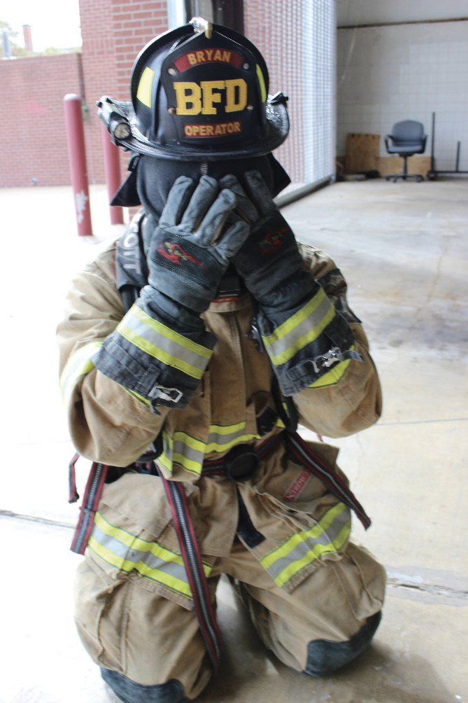 Pull the hood over your SCBA mask and use your hands to protect the mask from direct flames and heat.