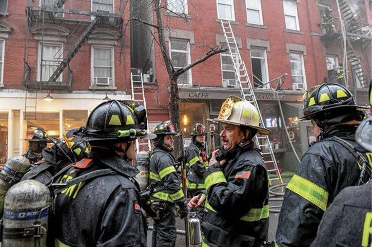 Directing the initial attack on arrival. Note the ground ladders positioned, which provided firefighter egress and were used to stretch hose raised to a second-floor window.
