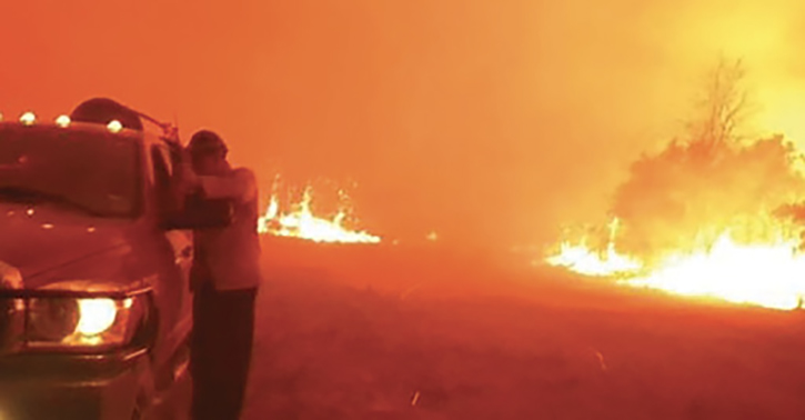 Firefighters wait out the initial flaming front from a safe position in front of the home.