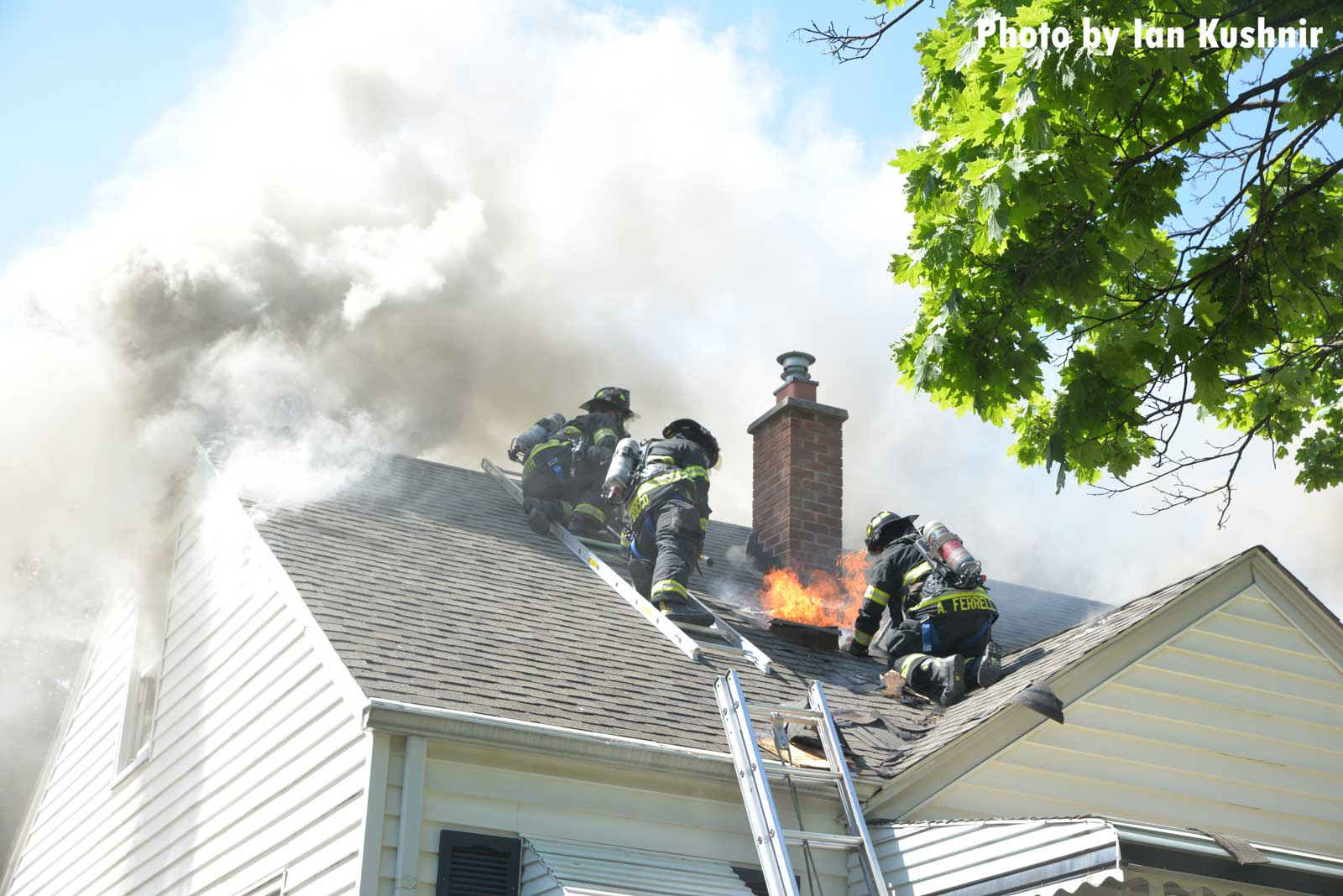 Firefighters perform vertical ventilation on the roof of a house fire