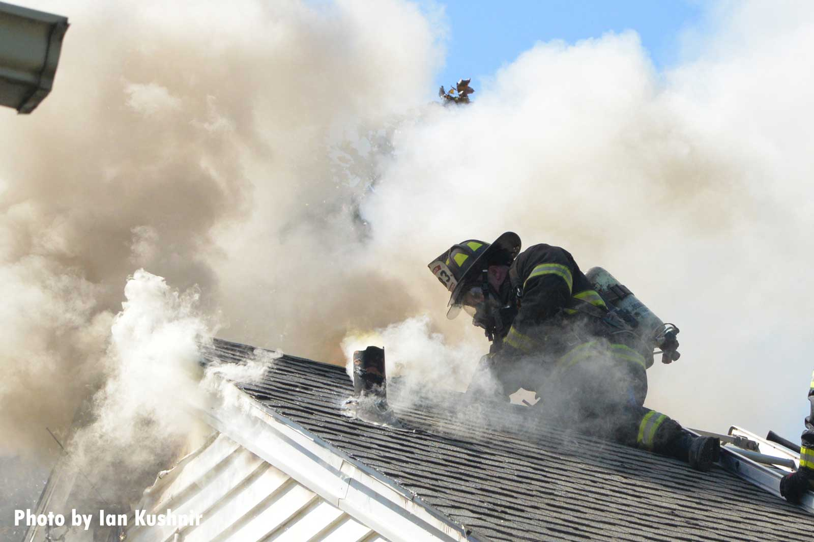 Firefighter on the roof of a home with smoke billowing about him