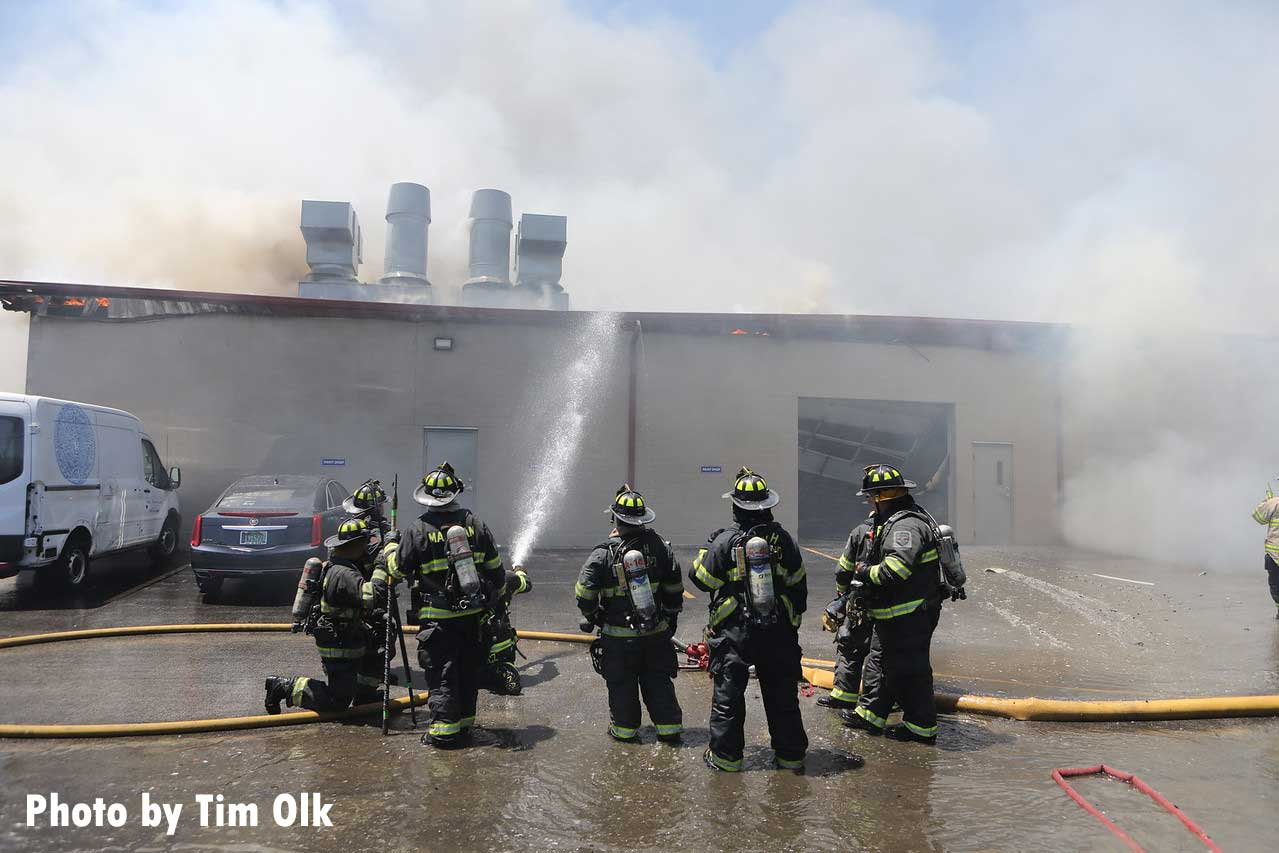 Firefighters conduct stream on exterior of building