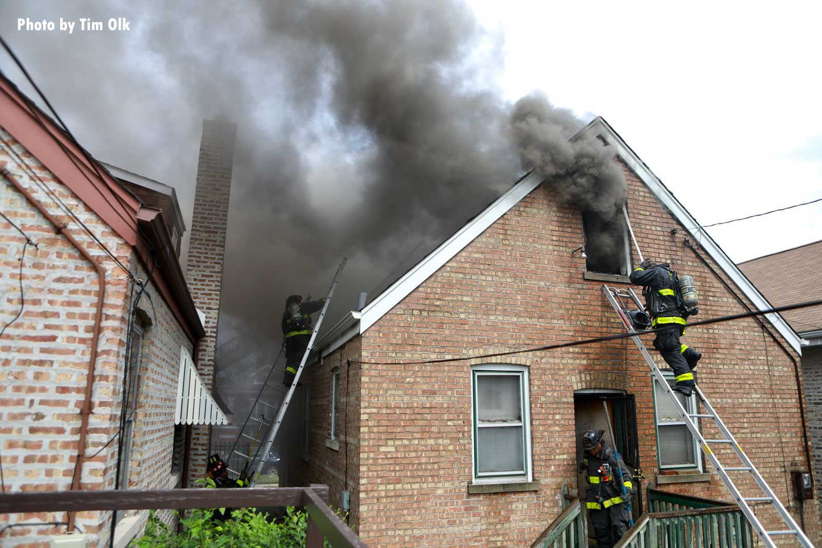 Dark smoke emerges from windows and roof of home