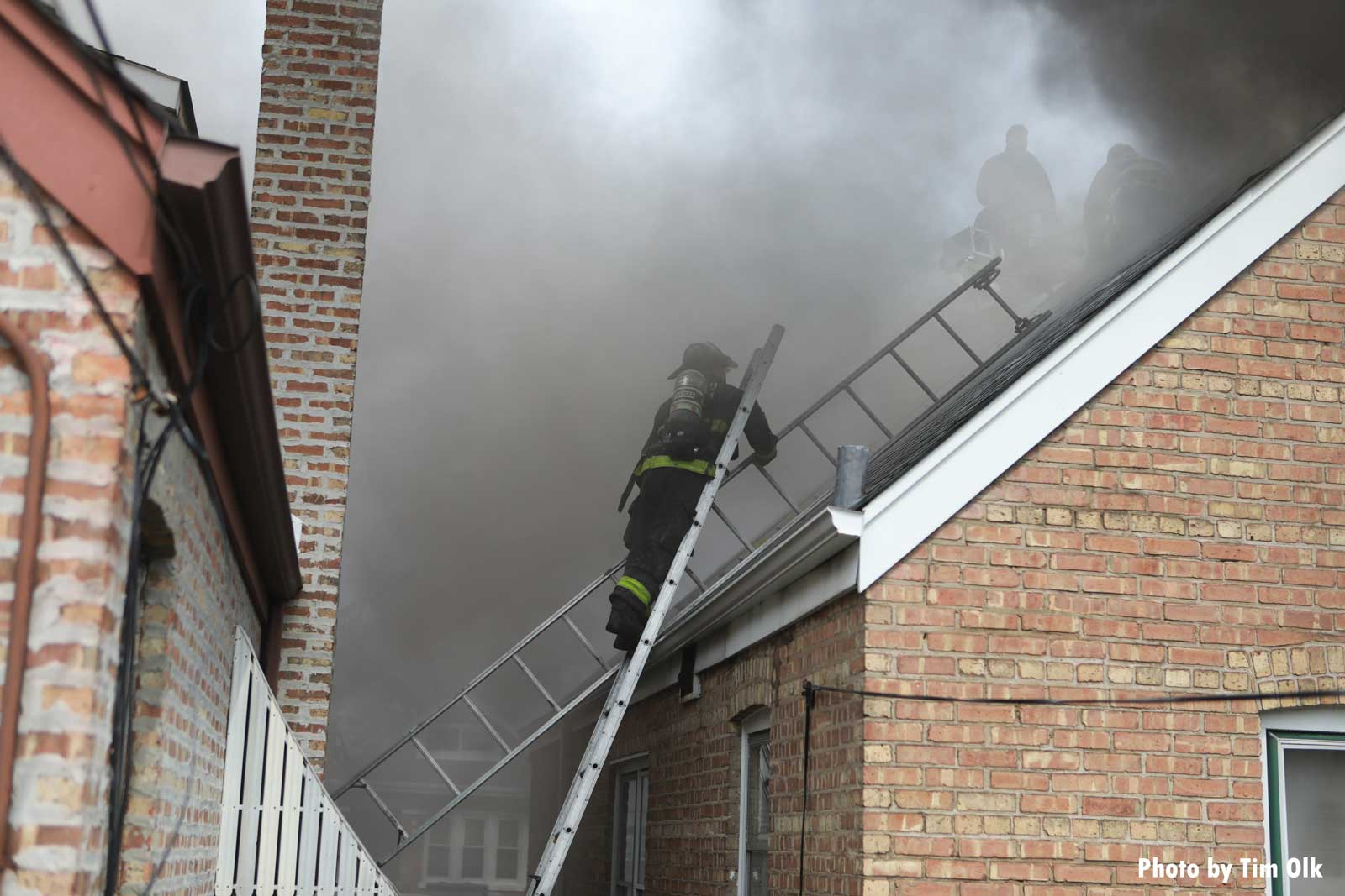 Firefighter brings ladders up to the roof