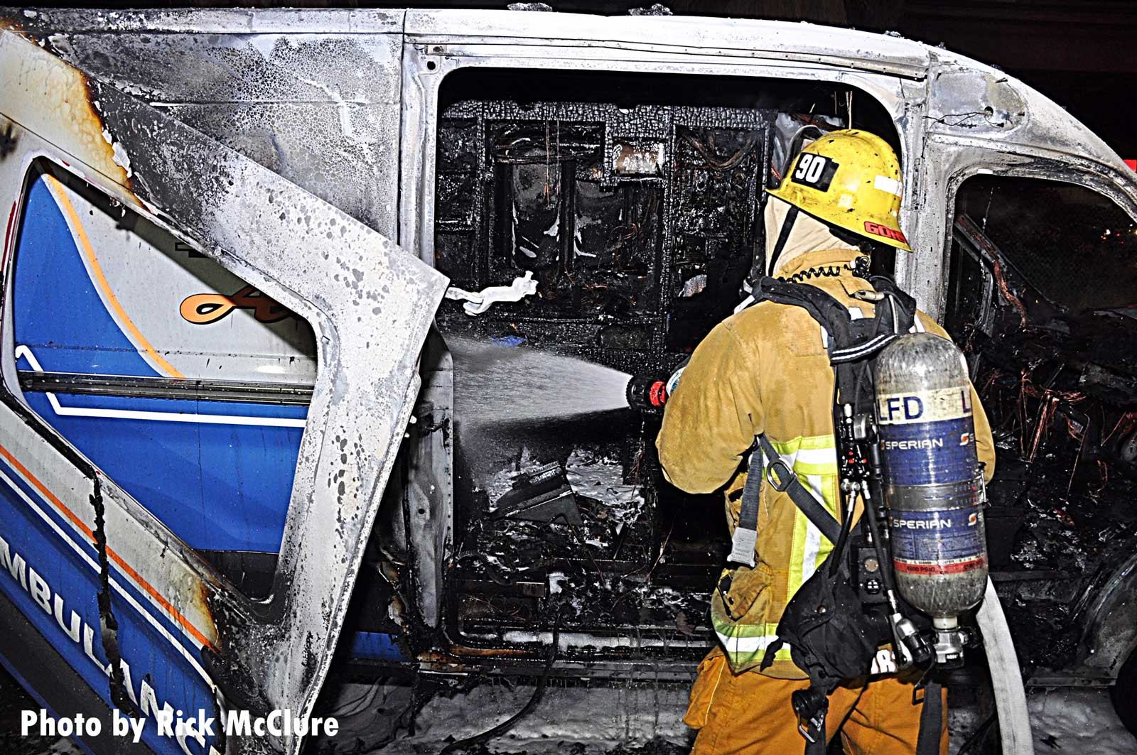 A firefighter aims a hoseline on the interior of the burned ambulance
