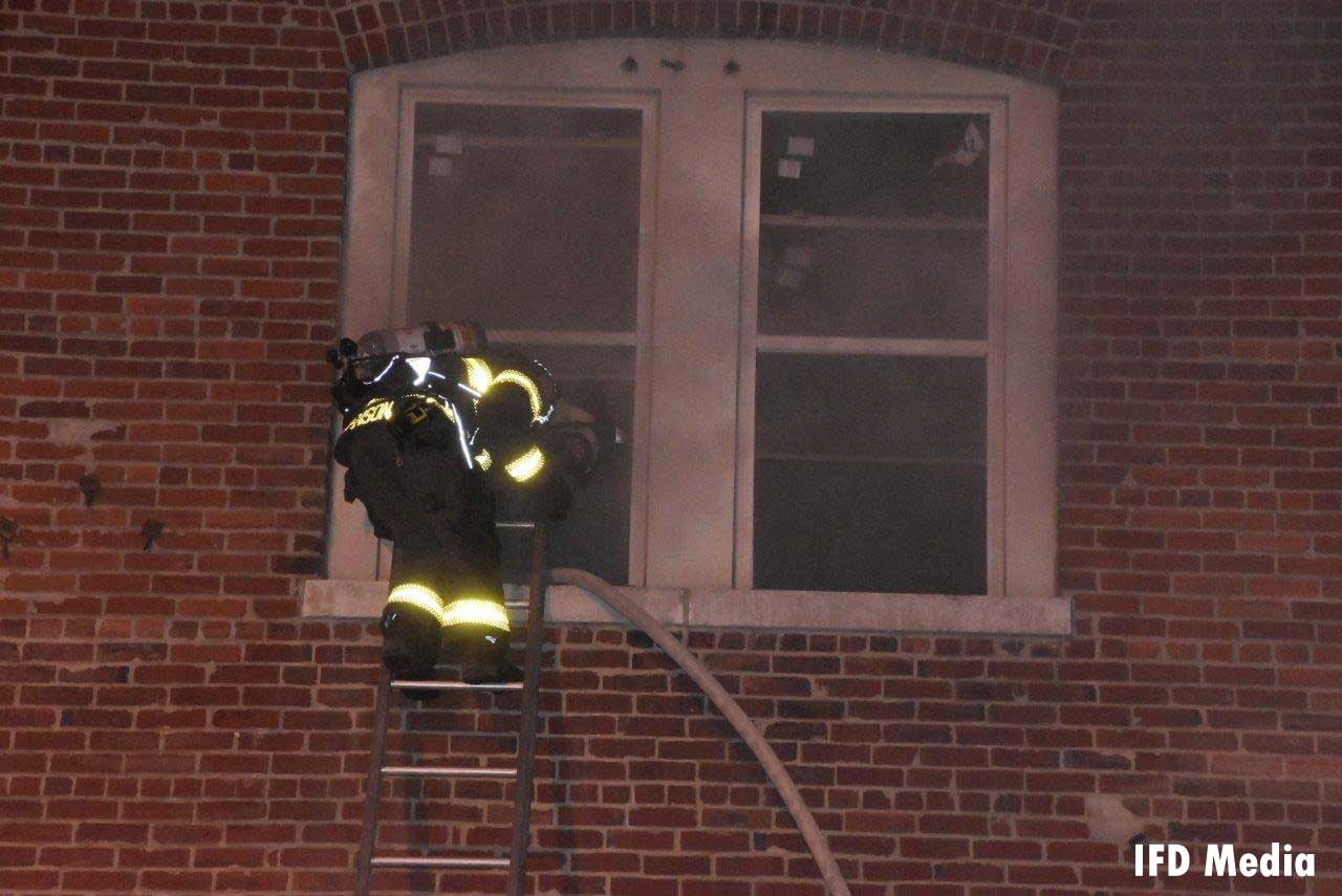 Firefighter on a ladder with a hoseline