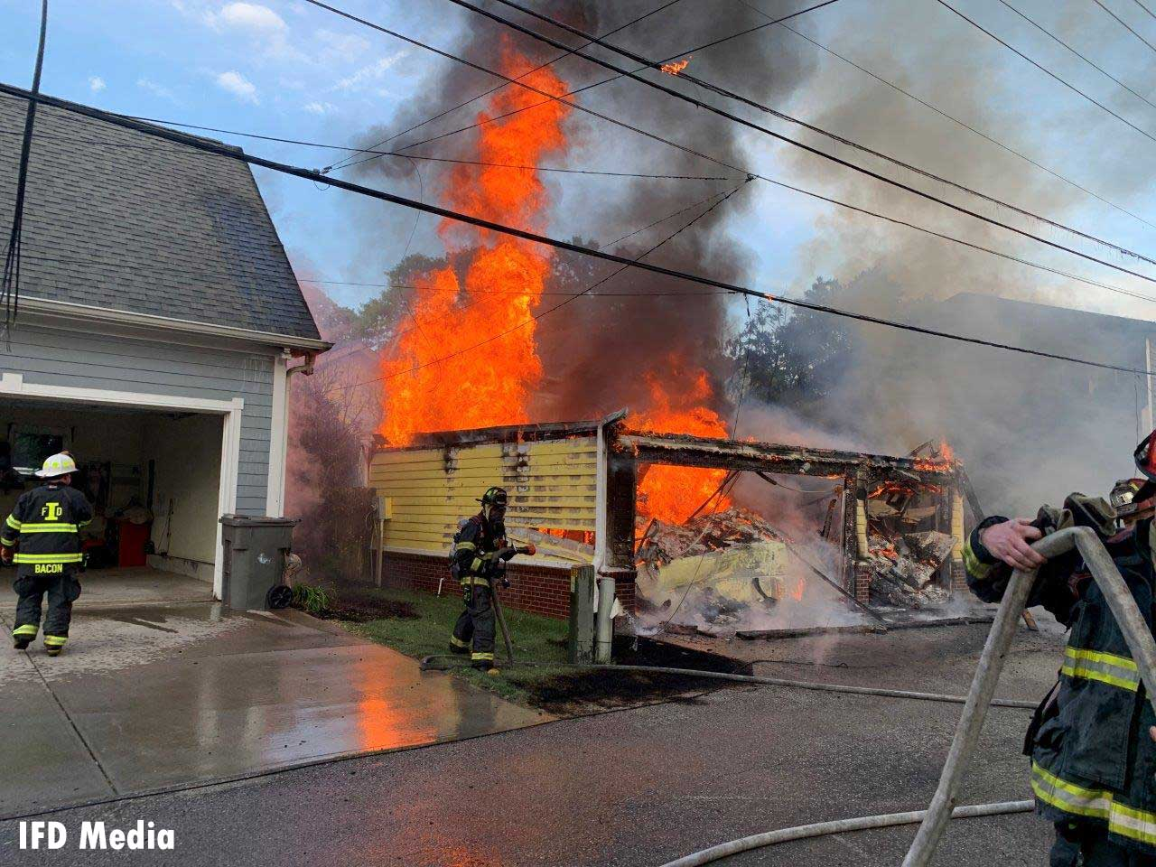 Flames shoot from a structure in Indianapolis as firefighters work