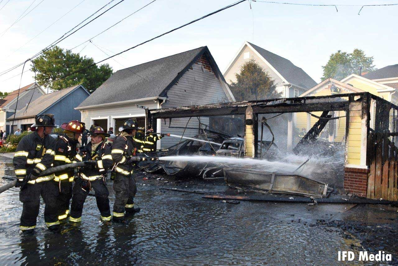 Firefighters work a hoseline on a charred out garage
