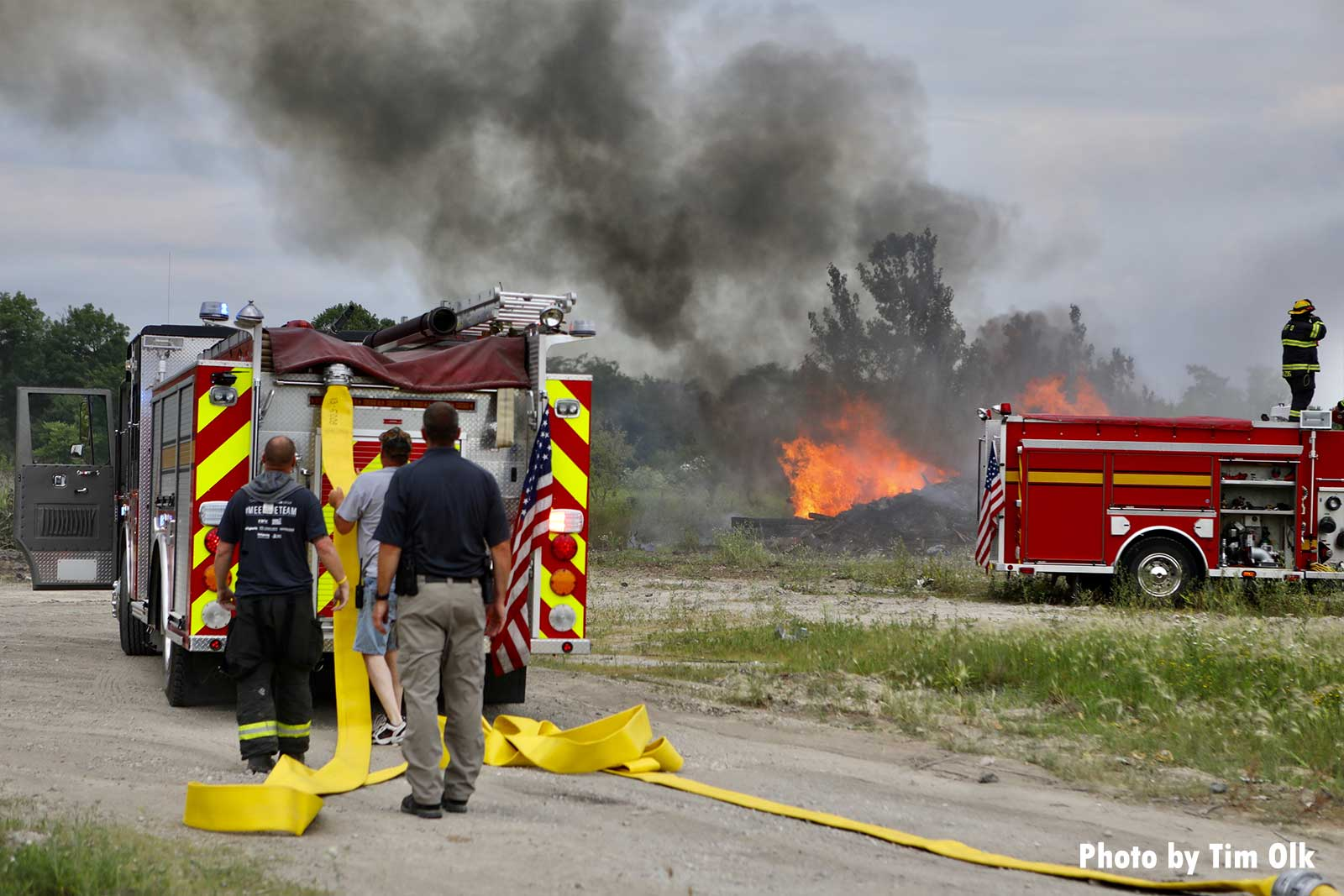 Rubbish fire burning with fire apparatus and firefighters