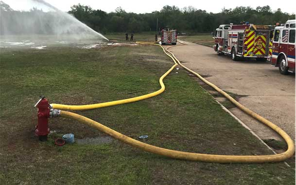 Two lines running into a fire hydrant with fire trucks