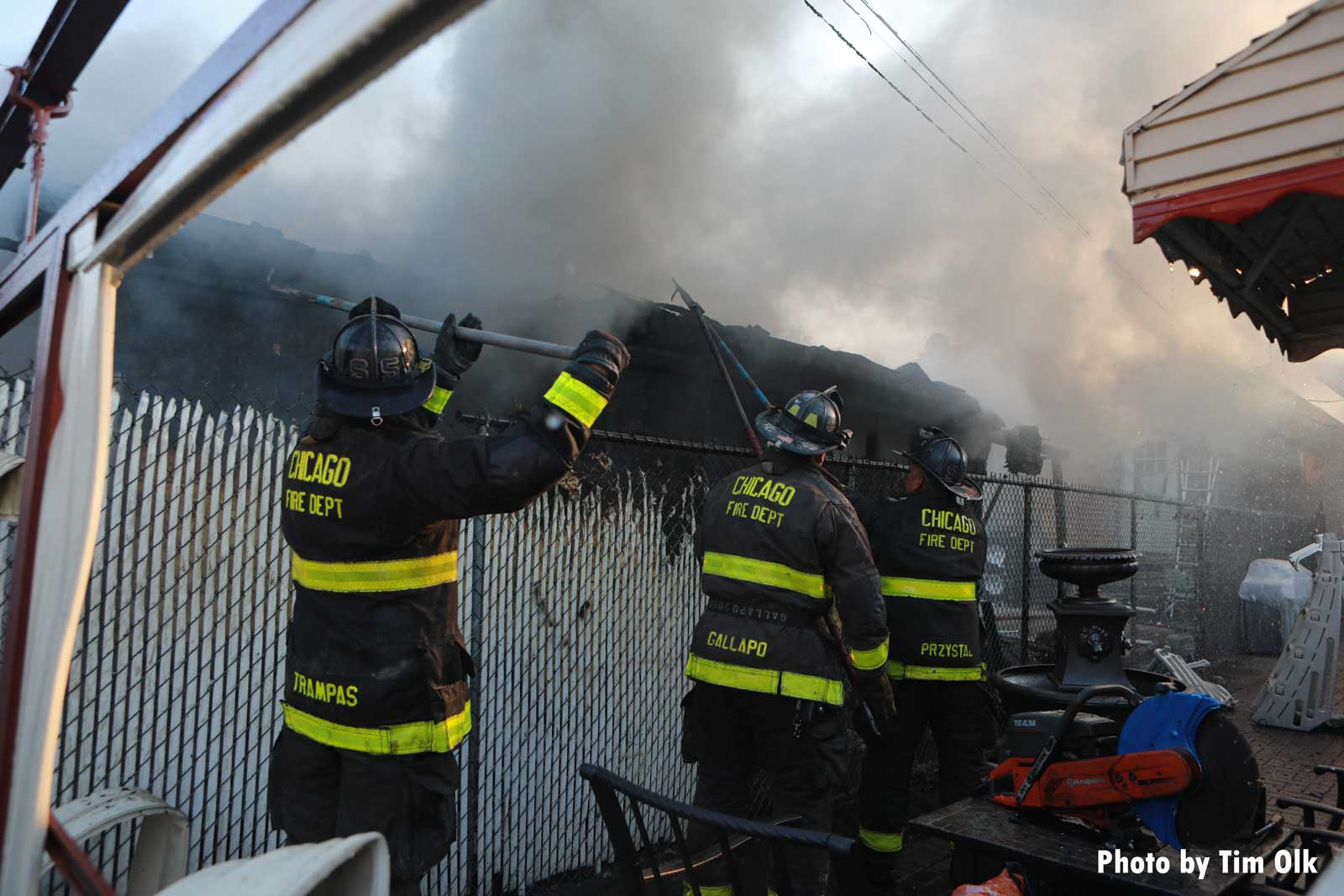 Multiple firefighters using hand tools at fire scene