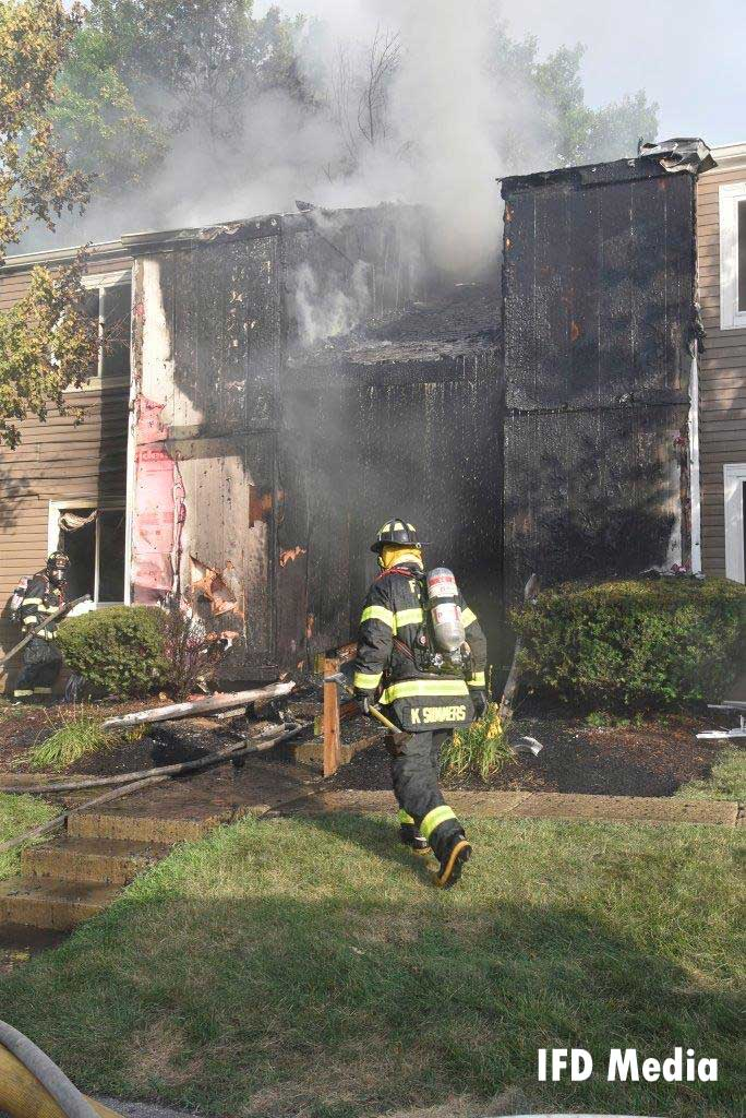 A firefighter advances toward a building with smoke showing