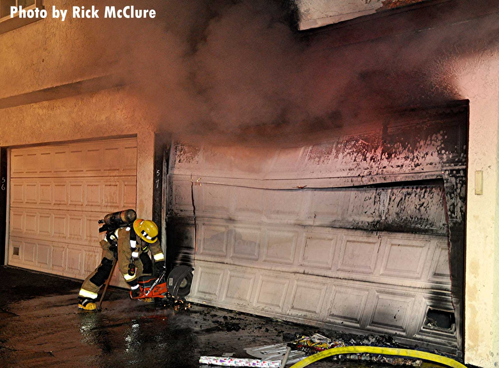 Smoke showing from garage with firefighter and tools